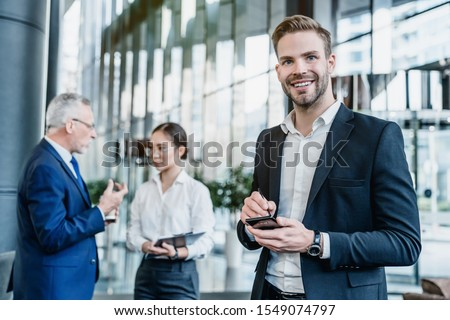 Portrait of smiling business man with smartphone in hands, his collegues on background Foto stock ©