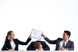 Portrait of smiling business partners holding document over head of their sleeping colleague