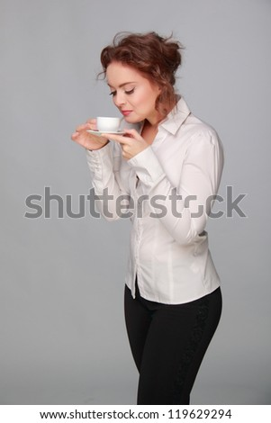 Portrait of smiling business woman, isolated on gray background with coffee cup on Food and Drink theme/Image of smiley business woman with coffee cup