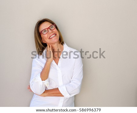 Portrait of smiling business woman with glasses looking up #586996379