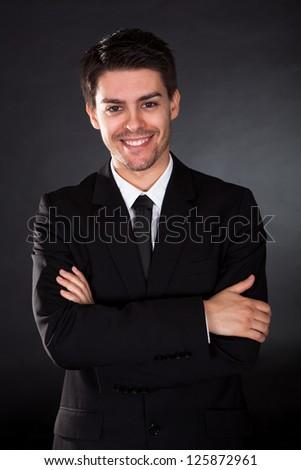 Portrait of smiling businessman over black background - stock photo