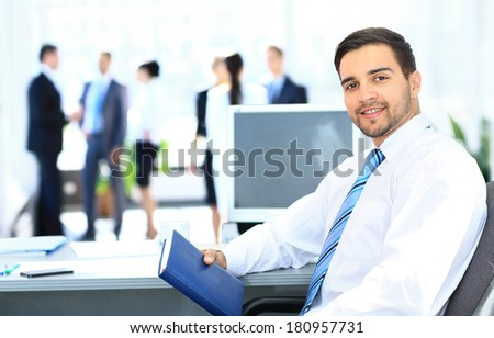 Portrait of smiling businessman working in office, looking camera - stock photo