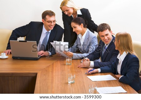 Portrait of smiling businesspeople discussing different questions sitting around the table with an opened laptop, documents and glasses on it
