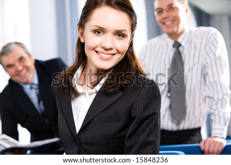 Portrait of smiling businesspeople with woman in front in the room