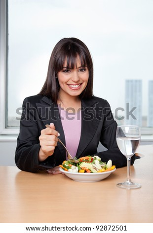 Portrait of smiling businesswoman having fresh vegetable salad with glass of water on desk