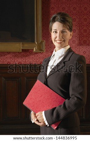 Portrait of smiling businesswoman holding book in conference room