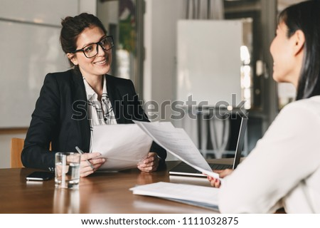 Portrait of smiling businesswoman holding resume and talking to female candidate during corporate meeting or job interview - business, career and placement concept