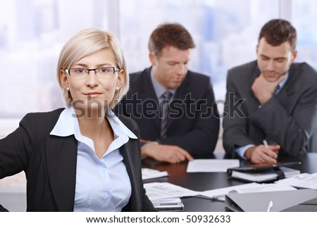 Portrait of smiling businesswoman in office with coworkers reviewing documents in background.