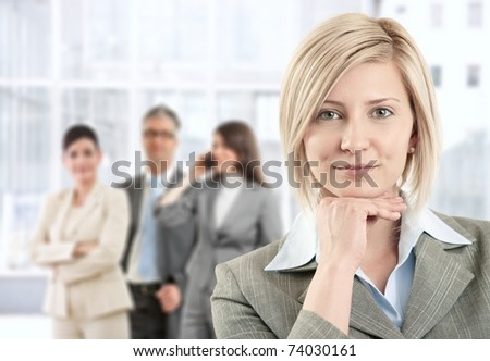 Portrait of smiling businesswoman posing at camera with team in background of office lobby.?