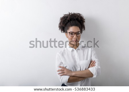 Portrait of smiling businesswoman standing against wall, corporate clothing
