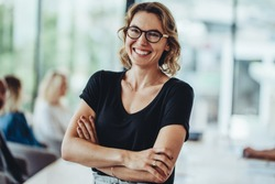 Portrait of smiling businesswoman standing in office with colleagues meeting in background. Successful female professional with her arms crossed in meeting room.