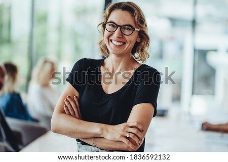 Portrait of smiling businesswoman standing in office with colleagues meeting in background. Successful female professional with her arms crossed in meeting room. Stock photo ©