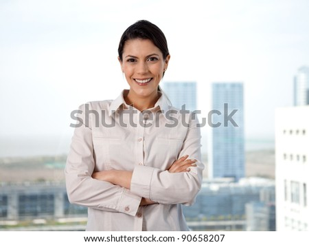 Portrait of smiling businesswoman with arms crossed standing in office