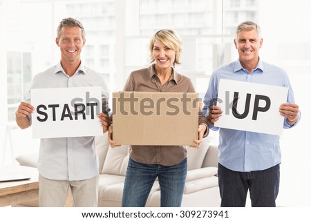 Portrait of smiling casual business people holding start up sign in the office