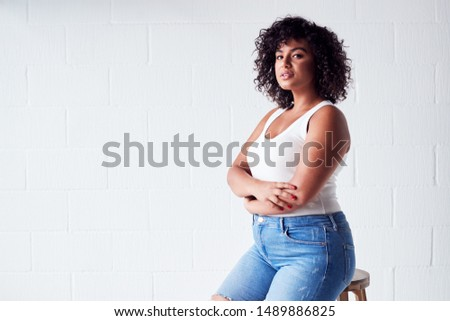 Portrait Of Smiling Casually Dressed Woman In Vest Top Standing Against White Brick Studio Wall