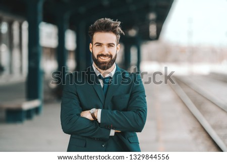 Portrait of smiling Caucasian bearded businessman in formal wear standing at train station with arms crossed. #1329844556