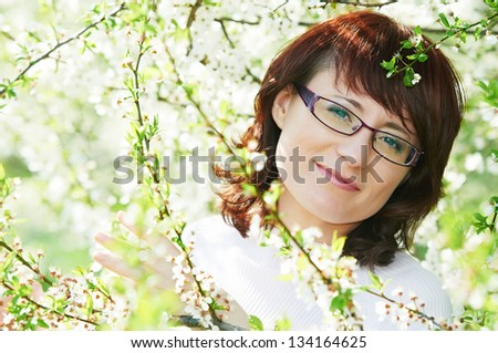 portrait of smiling caucasian brunette woman in spring cherry blossom tree garden outdoors