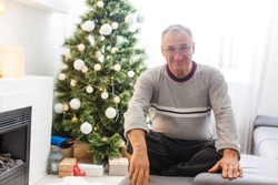 Portrait of smiling caucasian elderly man sitting ion the background of a Christmas tree at home