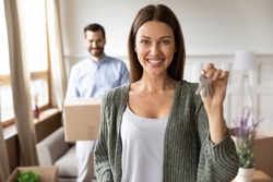 Portrait of smiling Caucasian woman show house keys move with husband to first shared own apartment. Happy wife renter relocate with man spouse to new home. Relocation, rental, realty concept.