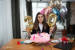 portrait of smiling Caucasian woman sitting at the table, birthday cake and number 30. Lady talking on webcam. Home alone birthday concept. Copy space.