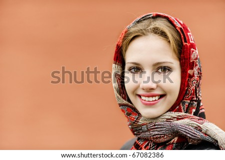 Portrait of smiling charming young woman in headscarf on red background.