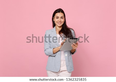 Portrait of smiling charming young woman in striped jacket using tablet pc computer isolated on pink pastel wall background in studio. People sincere emotions, lifestyle concept. Mock up copy space