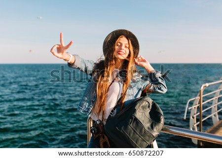 Portrait of smiling cheerful brunette girl in trendy hat posing in front of sea with peace sign. Adorable long-haired woman with leather backpack coming to ocean to make new photo and enjoy weekend