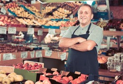 Portrait of smiling cheerful glad man seller who is standing in the vegetables store.