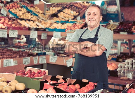 Portrait of smiling cheerful glad man seller who is standing in the vegetables store. - Shutterstock ID 768139951