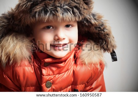 Portrait of smiling child in fur hood and orange winter jacket.fashion boy