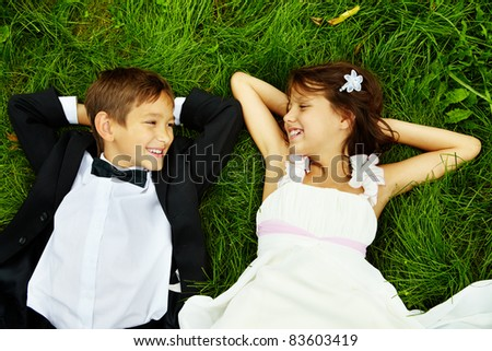 Portrait of smiling children bride and groom lying on green grass and looking at on another
