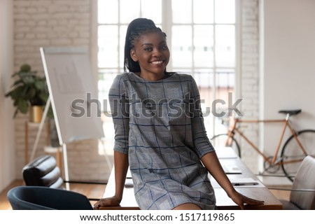 Portrait of smiling confident african american female company executive manager. Happy successful mixed race businesswoman team leader employee looking at camera, posing at modern creative office.