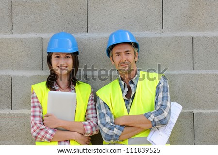 Portrait of smiling construction team standing on concrete wall