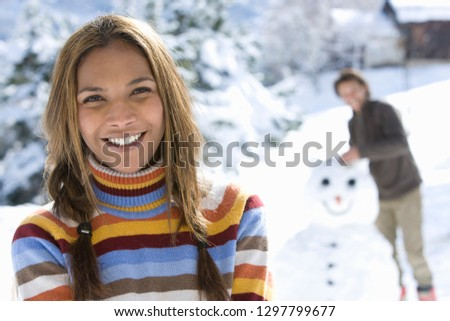 Portrait of smiling couple building snowman on winter vacation