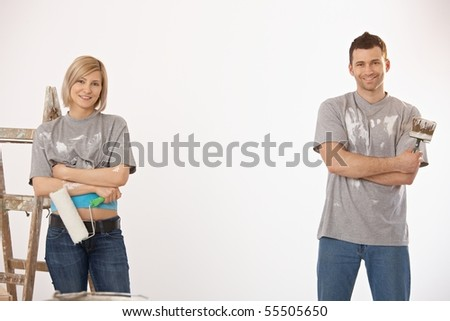 Portrait of smiling couple painting at home, holding paint roller and brush, looking at camera.
