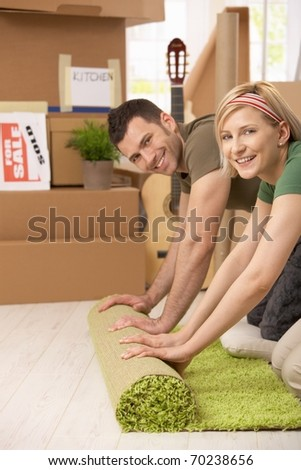 Portrait of smiling couple rolling out carpet together in new house.? - stock photo