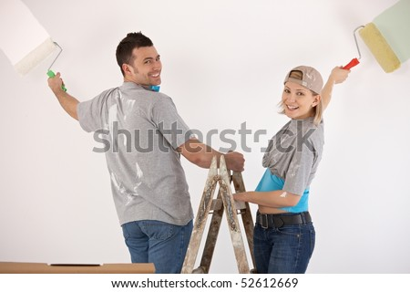 Portrait of smiling couple standing on ladder, painting wall together with paint roller.