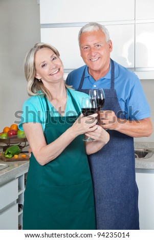 Portrait of smiling couple toasting wine glasses in the kitchen