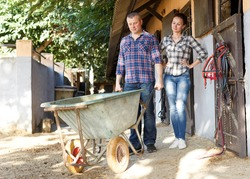 Portrait of smiling couple with barrow standing at horse stable outdoor