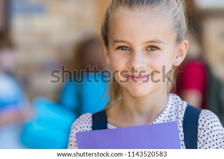 Portrait of smiling cute girl student holding book and looking at camera. Happy satisfied child wearing backpack at elementary school. Closeup face of blonde schoolgirl with school in background. #1143520583