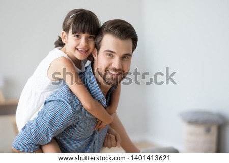 Portrait of smiling cute little preschooler girl piggyback young father looking at camera, loving dad carry funny small daughter on back, posing for picture together, parent and child hug make photo