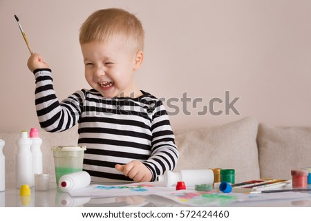Stock Photo Portrait of smiling cute toddler boy drawing at home with colorful paints and brush. Creative child having fun. Educational concept