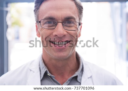 Portrait of smiling dentist with eyeglasses at clinic - Shutterstock ID 737701096