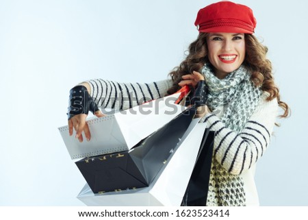 Portrait of smiling elegant 40 years old woman with long brunette hair in sweater, scarf and red hat holding shopping bags on winter light blue background.