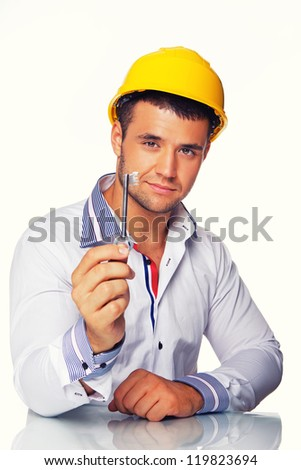 Portrait of smiling engineer posing in studio with key from house - stock photo