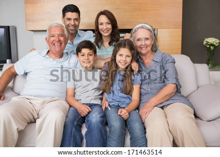 Portrait of smiling extended family sitting on sofa in the living room at home