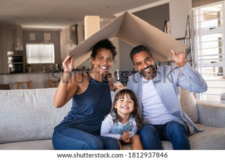 Portrait of smiling family sitting on couch holding cardboard roof and looking at camera. African and indian parents with daughter holding cardboard roof over heads while sitting on sofa in new home