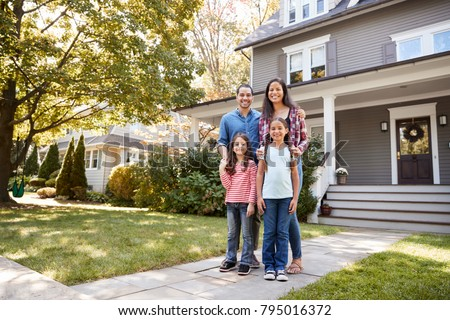 Portrait Of Smiling Family Standing In Front Of Their Home