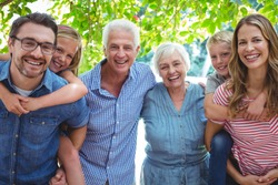 Portrait of smiling family with grandparents standing against tree