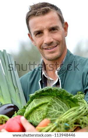 Portrait of smiling farmer holding vegetables basket